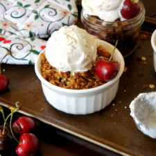 Cherry Crisp in a small dessert bowl topped with a scoop of ice cream with a fresh cherry on top