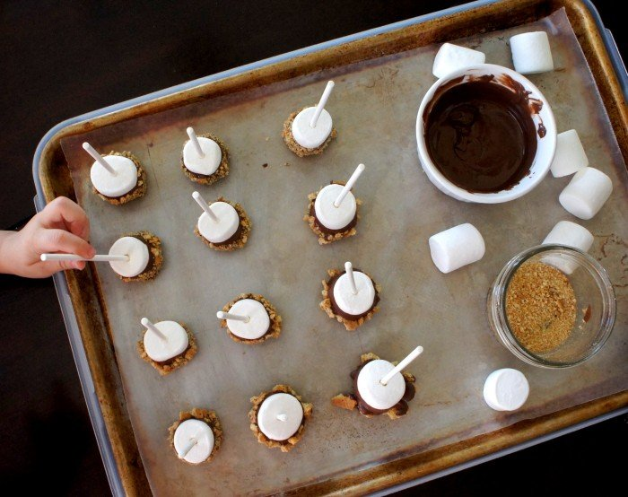 A look down on a pan of marshmallow pops drying on a pan next to a bowl of chocolate sauce and graham cracker crumbs
