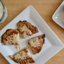 A plate with a sliced Cauliflower Crusted Pizza on it.