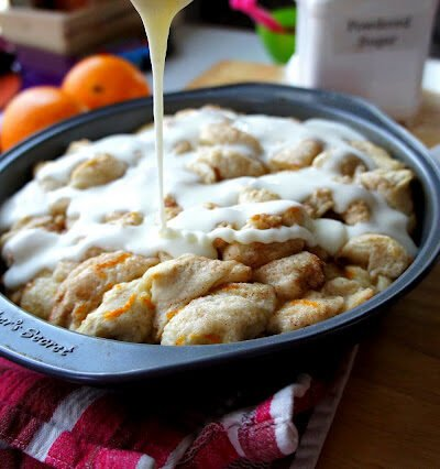 Icing being drizzled on top of a round pan of Orange Cinnamon Pull Apart