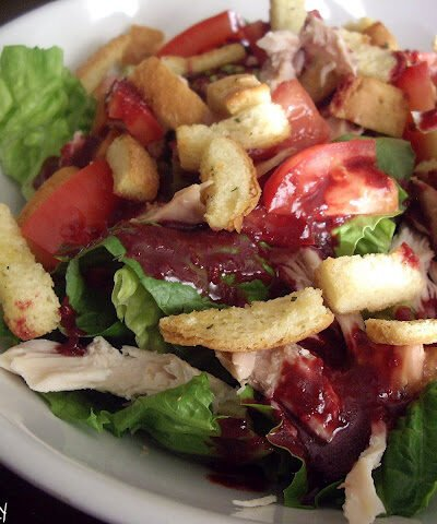 Salad topped with tomatoes and croutons in a bowl.