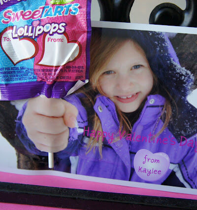 A close up of a Valentine's Day card; picture of little girl holding hand out with a lollipop attached to the picture.