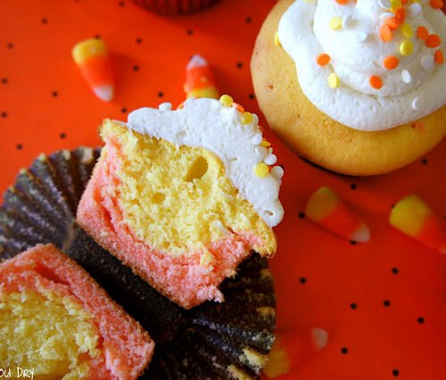 A candy corn styled cupcake sliced in half, displayed next to other candy corn cupcakes