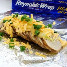 Sliced potato slices on tinfoil topped with shredded cheese and chives