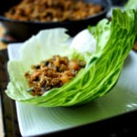 Chinese chicken mix laying in a leaf of lettuce displayed on a plate