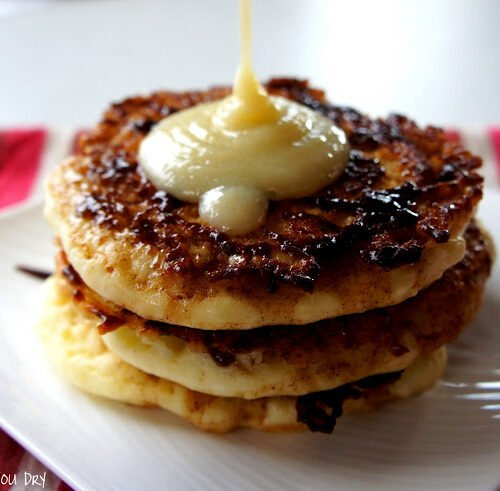 A close up of a display of three pancakes on a plate being topped with a syrup.