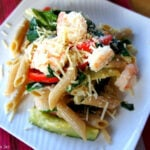 A close up of pasta displayed on a plate  topped with veggies, shrimp and cheese