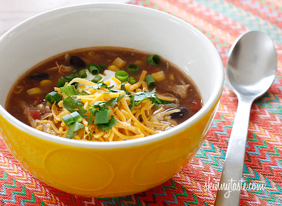 A bowl of Enchilada Soup on a table, topped with shredded cheese and cilantro