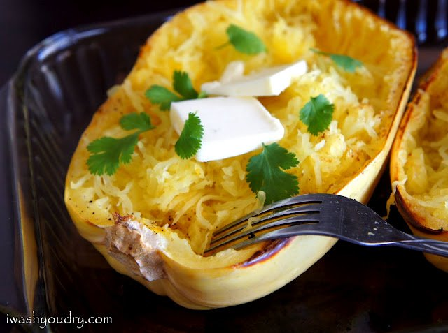 Half a baked Spaghetti Squash with a couple squares of melting butter and fresh herbs on top