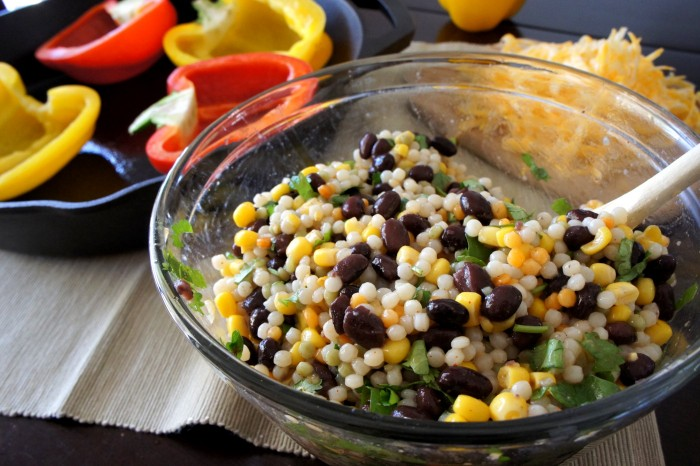 Couscous and beans mixed together in a glass bowl.