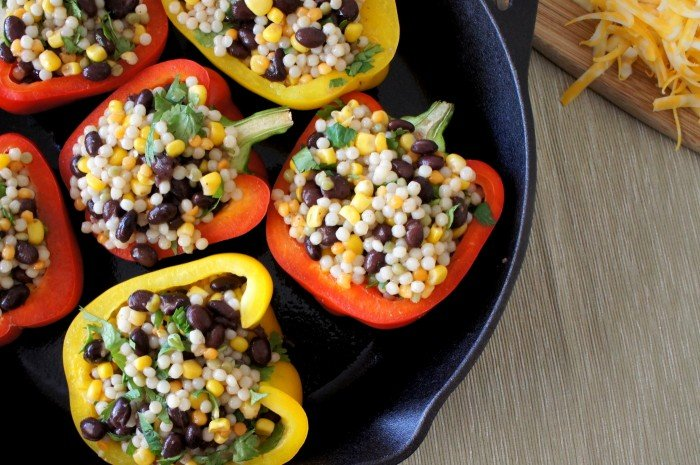 A close up of the peppers stuffed with couscous, and beans in a skillet