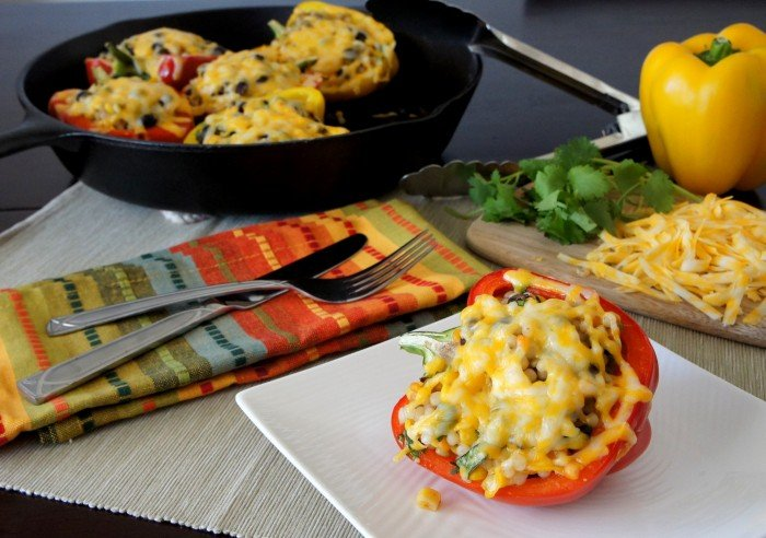A stuffed bell pepper covered with melted cheese on a plate displayed on a table in front of a pan of more stuffed peppers
