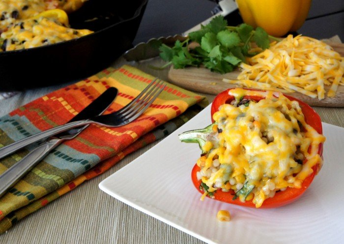 A stuffed bell pepper covered with melted cheese on a plate displayed on a table