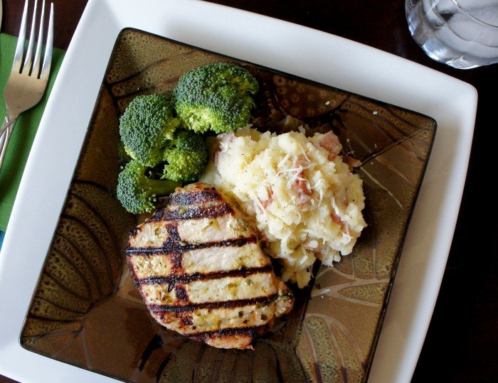 A plate with a grilled pork chop and sides of mashed potatoes and broccoli