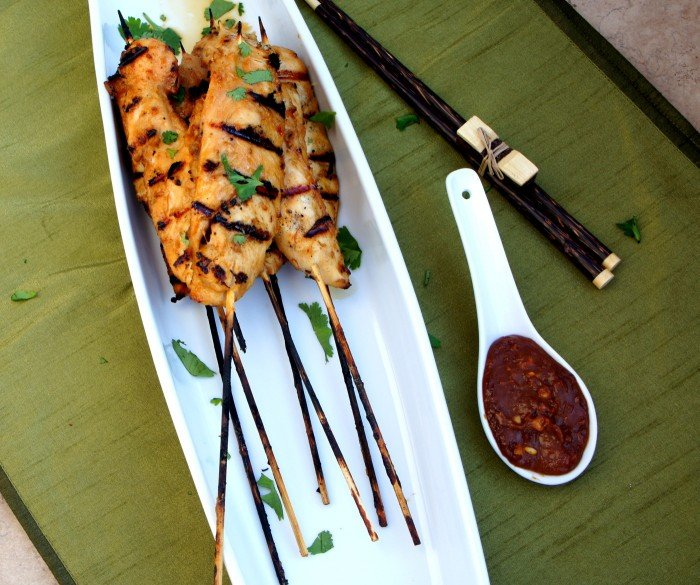 Thai Chicken Satay Skewers on a plate next to a small bowl of Spicy Peanut Dipping Sauce