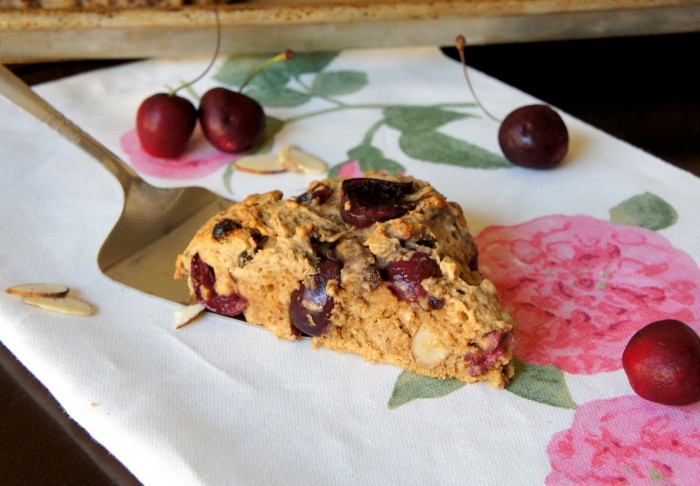 A slice of a cherry scone being placed on a napkin