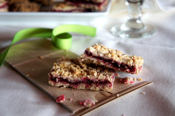 Two raspberry crumble bars displayed on a table