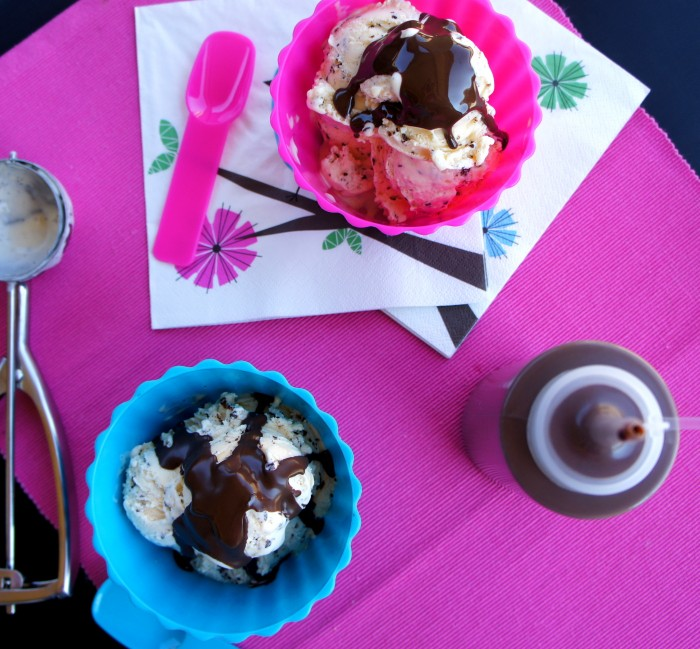 Two bowls of ice cream topped with chocolate sauce next to a bottle of homemade chocolate sauce