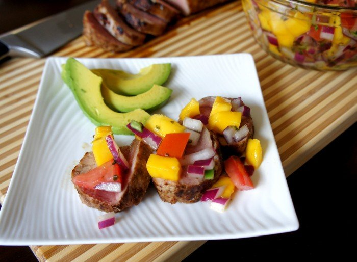 A plate with sliced pork tenderloin topped with a mango salsa and a side of avocado slices