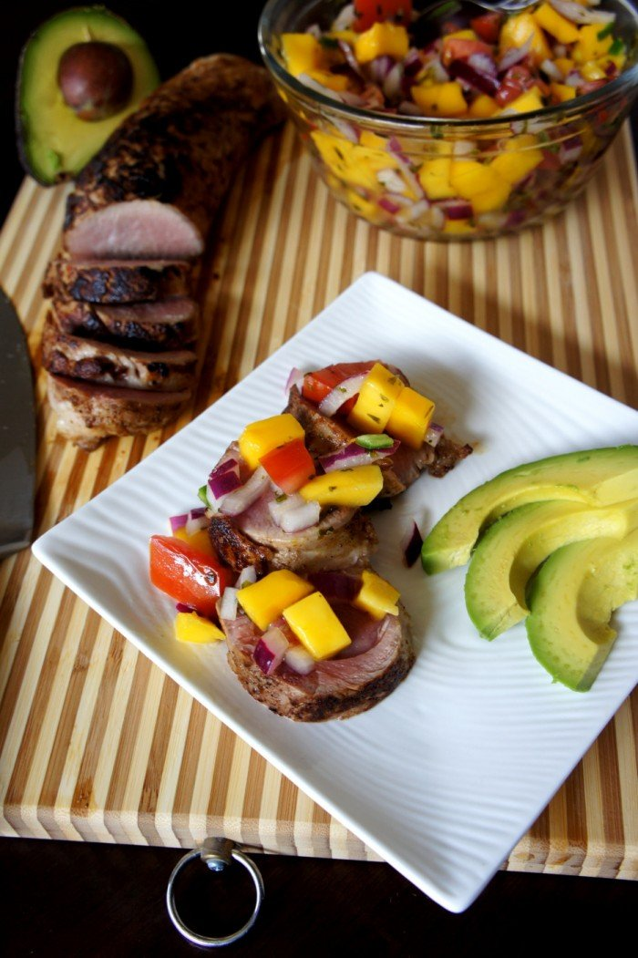 Sliced pork tenderloin on a plate topped with mango salsa and a side of avocado.