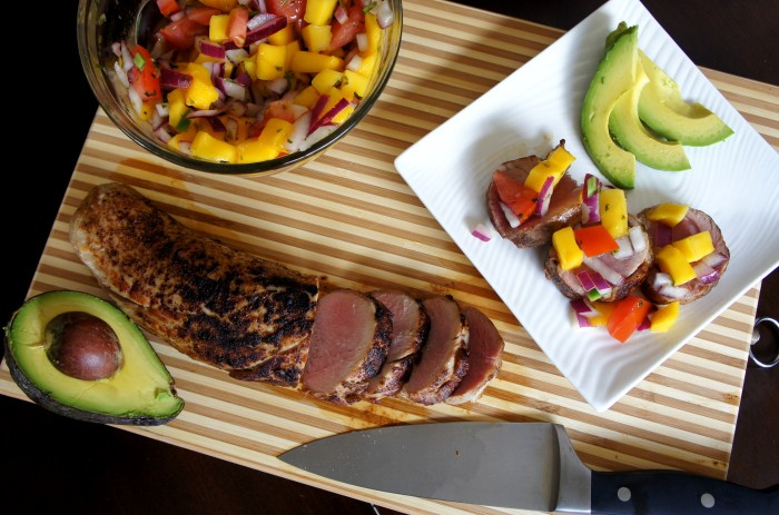 A look down on a cutting board with a pork tenderloin with a few slices, a plate of plated food and a bowl of mango salsa