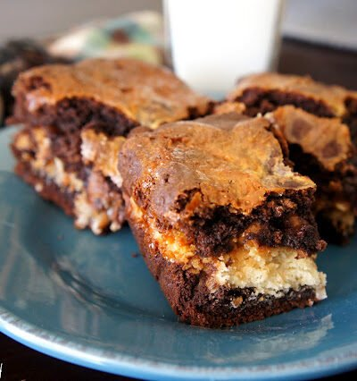 Three brownie squares on a plate next to a glass of milk