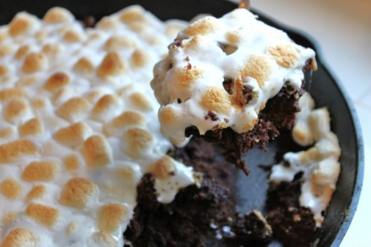 Brownies baked on a skillet topped with melted marshmallows with a slice being removed