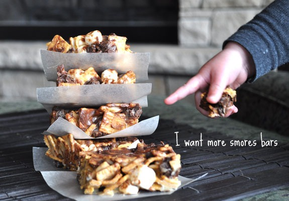 S\'mores bars stacked on top of each other with a little hand pointing to them