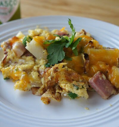 A plate displaying food; with ham, potatoes, eggs and cheese.