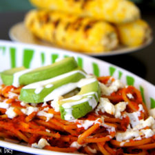 A bowl of red pasta with slices of avocado on top drizzled with a white sauce
