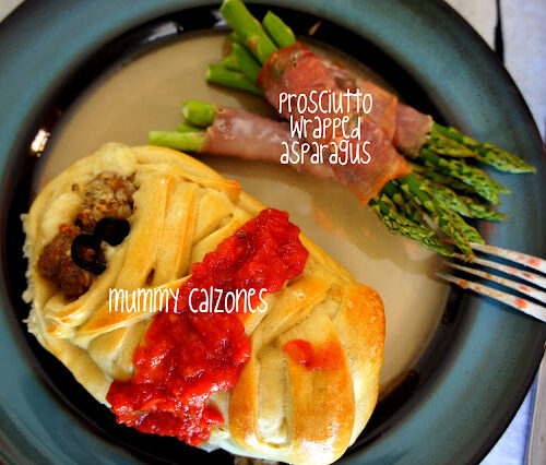 A mummy shaped calzone, topped with a little sauce on a plate next to bacon wrapped asparagus