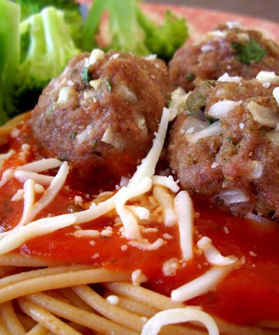 Meatballs on top of spaghetti noodles and a red sauce with side of broccoli.