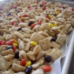 A baking pan of cereal and Reeses pieces.