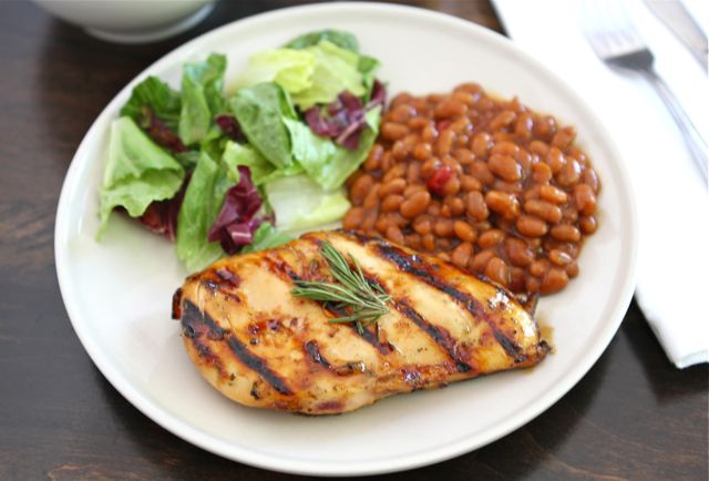 Lemon, Honey & Rosemary Grilled Chicken on a plate, with a side of baked beans and salad