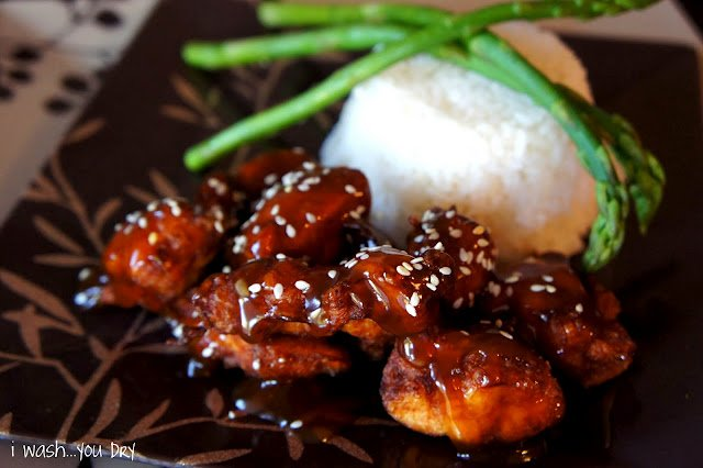 Sesame Chicken on plate next to a side of rice and asparagus sticks