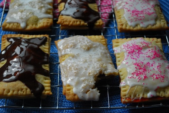 Homemade pop tarts with frosting on them resting on a cooling rack.