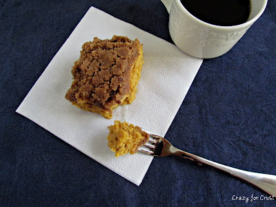 A piece of Pumpkin Coffee Cake on a napkin with a fork next to it with a bite of the cake on it.
