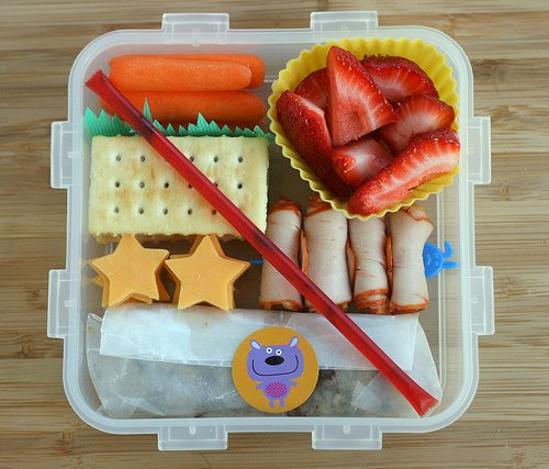 A bento lunch idea with carrot sticks, strawberry slices, crackers, star shaped cheese slices and rolled meet