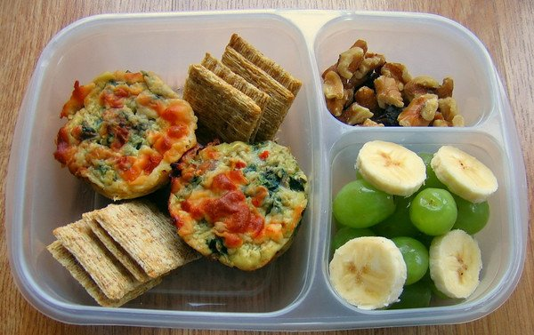 Bento lunch idea with a compartment for walnuts, a compartment for grapes and banana slices and crackers