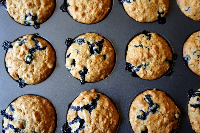 Close up of a pan of muffins, with blueberries drizzling from them