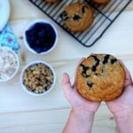 Two hands holding a Blueberry & Walnut Muffin above a table