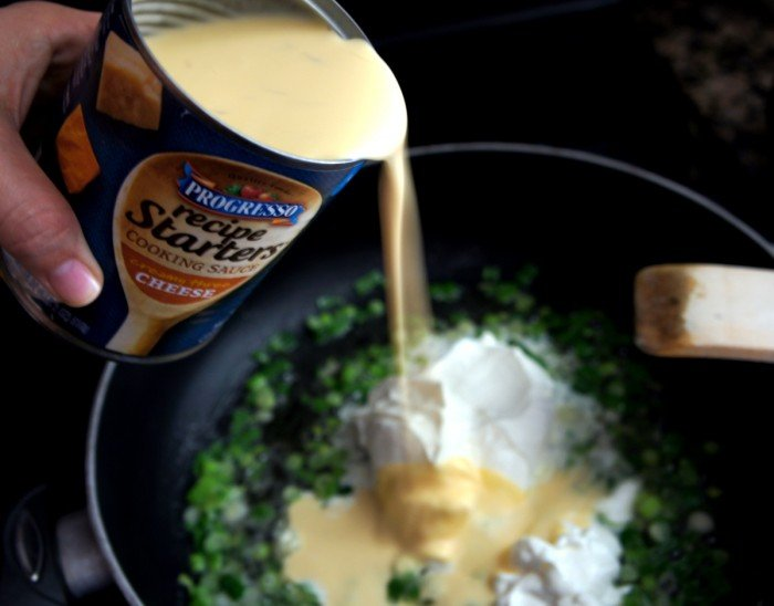 A pan with green onions, sour cream and a can of cheese being poured into it.