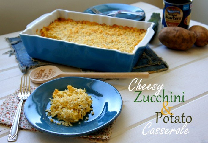 A scoop of casserole on a plate in front of a pan of Cheesy Zucchini and Potato Casserole