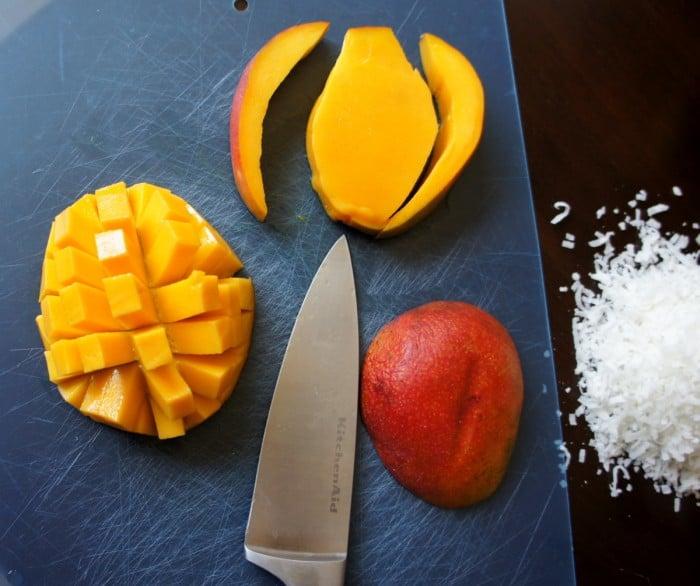 Mango sliced on a cutting board with a knife