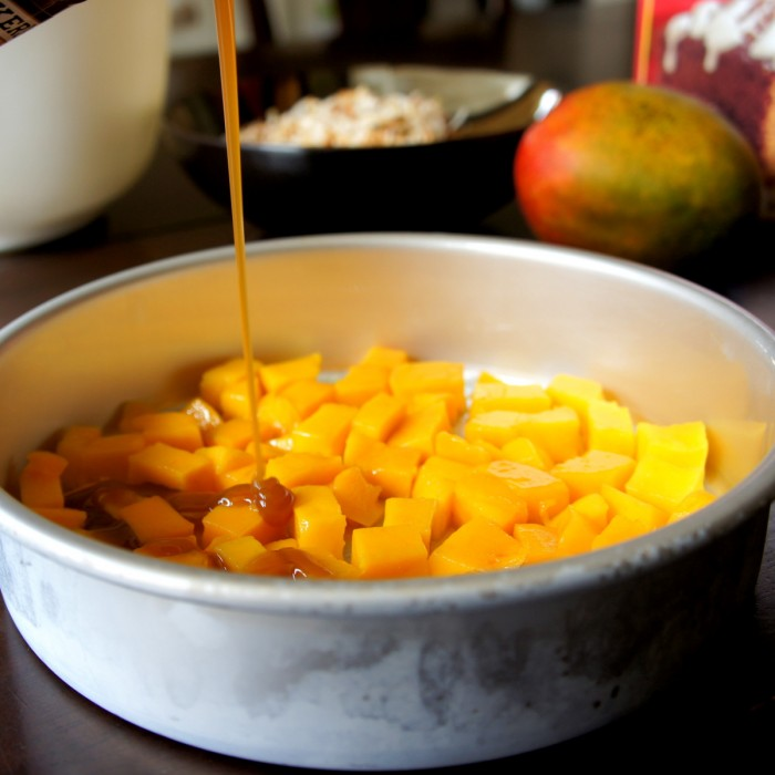 Cubed mangos in the bottom of a cake pan being drizzled with caramel sauce