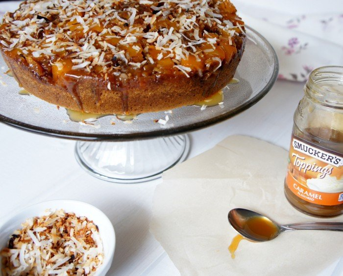 An upside down mango cake displayed on a clear glass cake plate  topped with caramel and coconut flakes