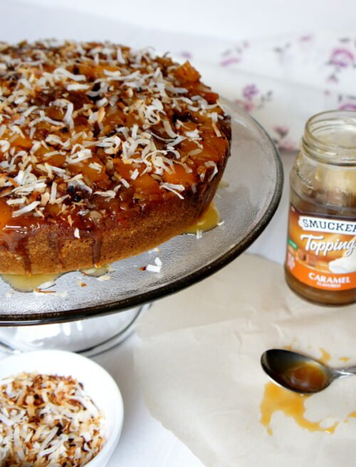 A cake on a cake platter topped caramel and coconut flakes