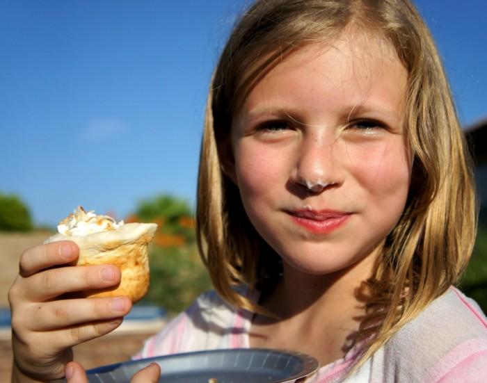 A girl eating a campfire tart