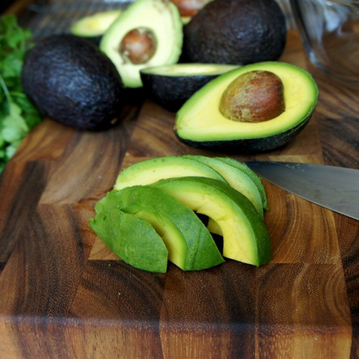 A sliced avocado on a cutting board in front of many halves of an avocado