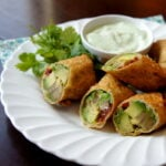 Veggie egg rolls cut in half with a side of dip
